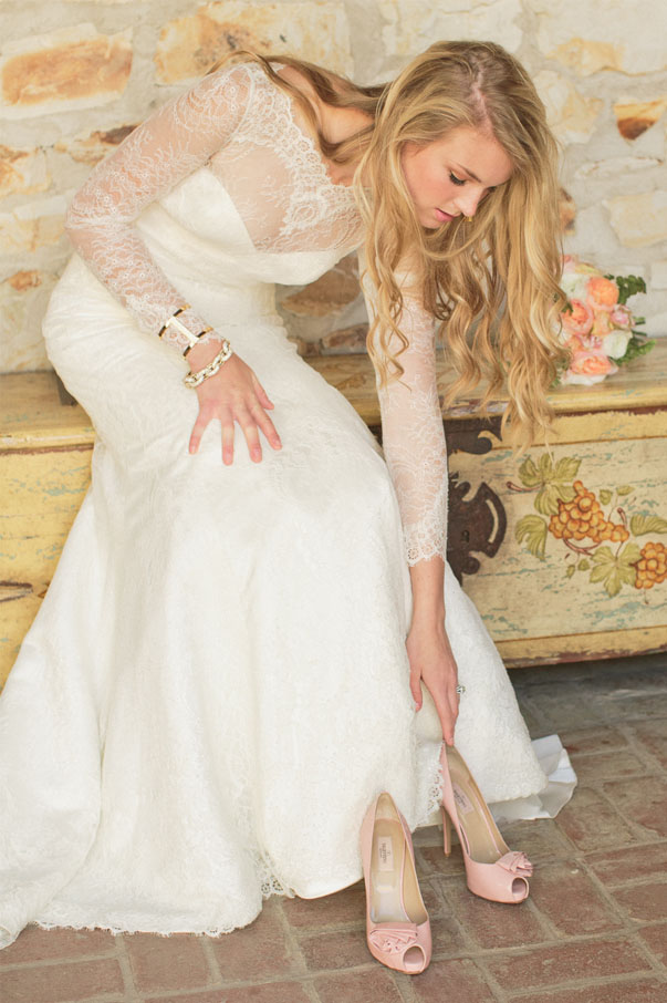 candid wedding photo of the bride moments before putting her shoes on to walk down the aisle