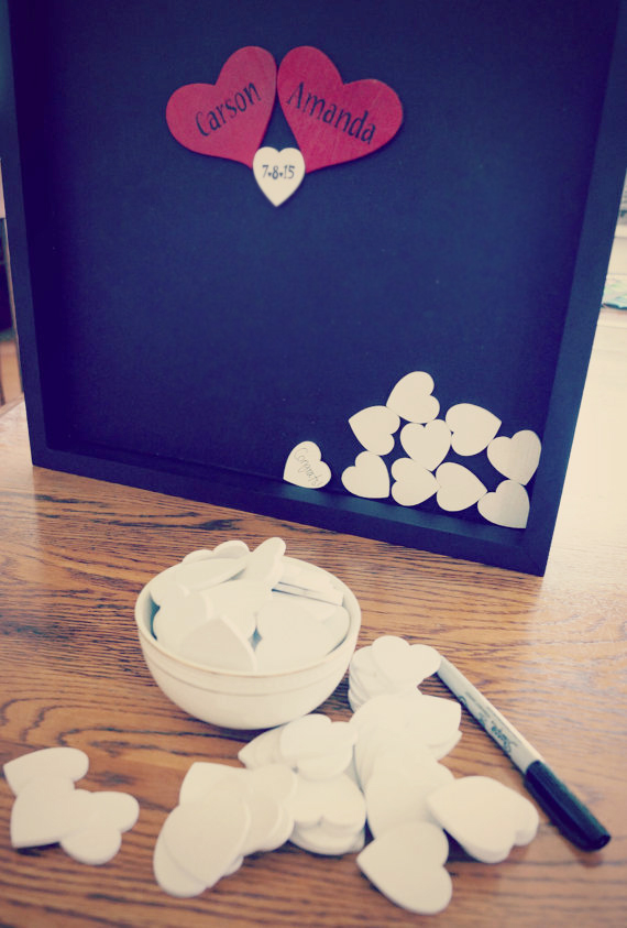 A handmade unique wedding guestbook in a form of a drop top frame and wooden hearts