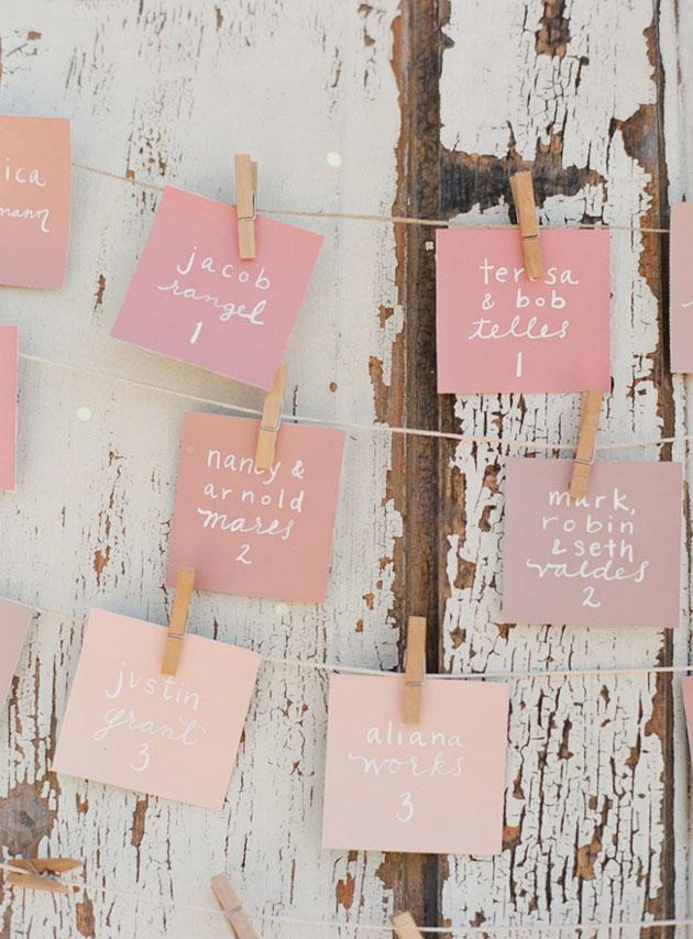 pink handwritten seating chart hanging on twine