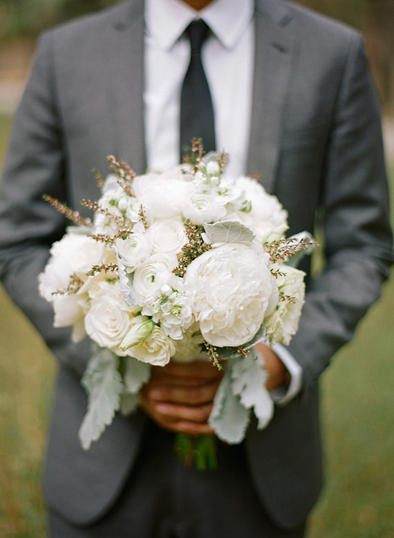 A cute must have photo of the groom holding the bride's bouquet