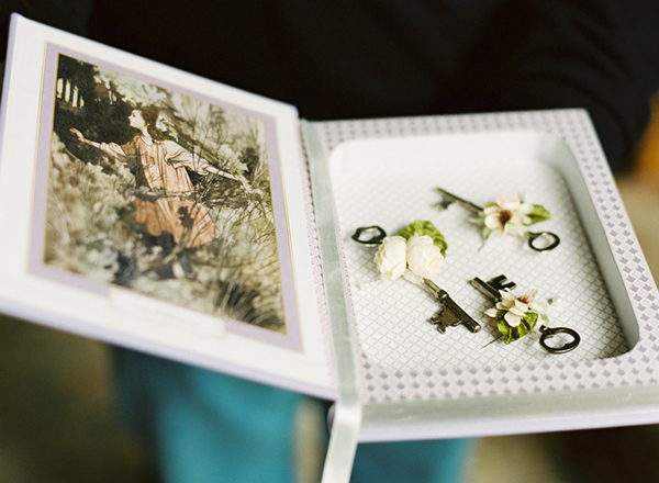 "How adorable is this idea? The wedding theme was ""Secret Garden"" so the bride wore a headpiece with little keys woven into it while the groomsmen wore keys as boutonnieres. Such a beautiful idea! The groomsmens' boutonnieres are shown above in a hollow book cover of ""The Secret Garden."""